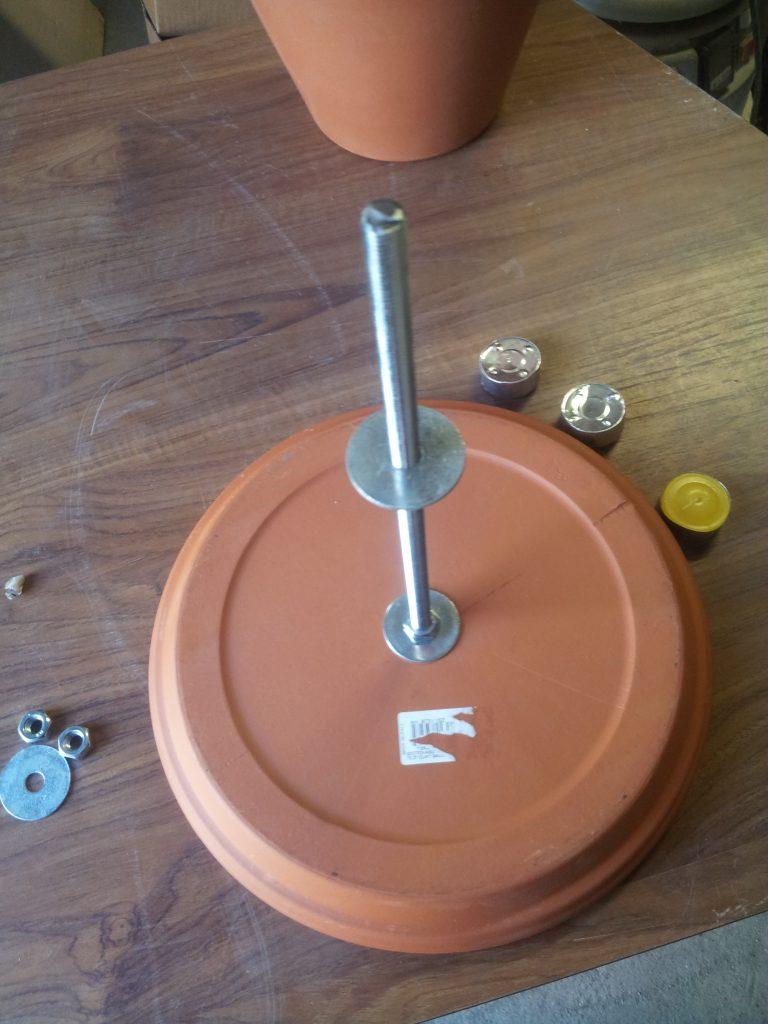 mise en place de l'écrou et rondelle pour le premier pot de fleurs chauffage terre cuite
